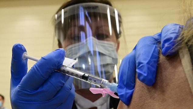 Une femme masquée administre un vaccin.