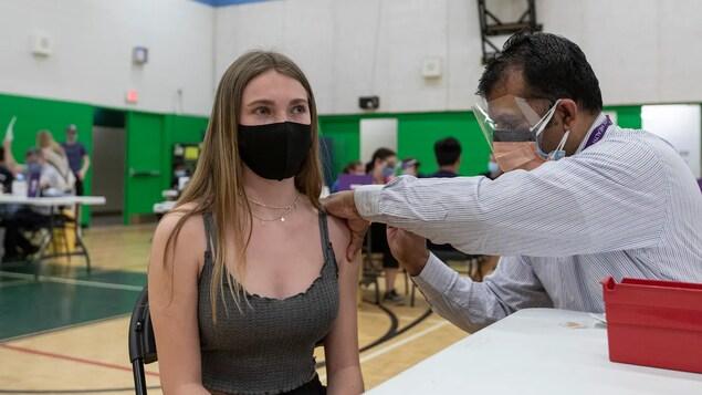 Une adolescente dans le gymnase de l'école reçoit son vaccin dans l'épaule.