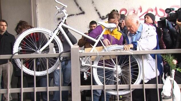 Des gens sont réunis autour du vélo peint en blanc en hommage à la cycliste Mathilde Blais