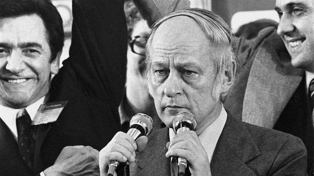 René Lévesque devant deux micros, le 15 novembre 1976. Camille Laurin se trouve en arrière-plan.