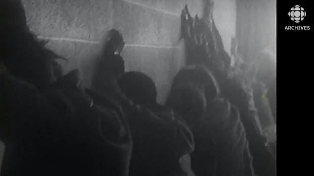 Des manifestants sont plaqués face à un mur durant l'émeute à l'Université Sir-George-Williams le 11 février 1969.