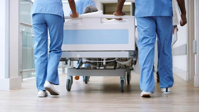 Des membres du personnel d'un hôpital transportent un patient sur une civière.