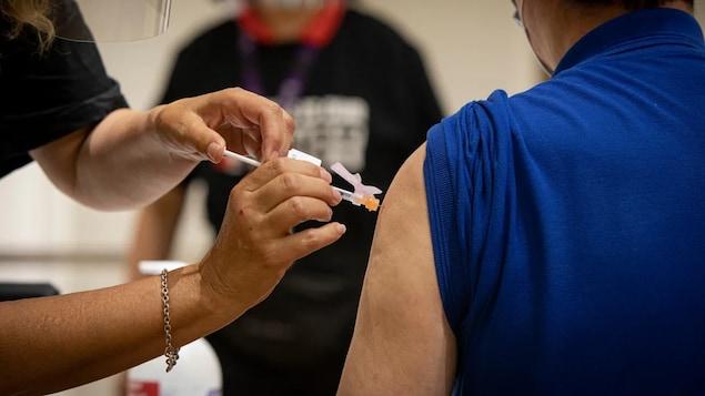 Une personne se fait administrer un vaccin contre la COVID-19.