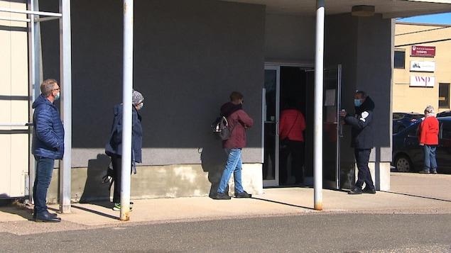 Des gens font la file à l'extérieur pour avoir accès au site de vaccination.