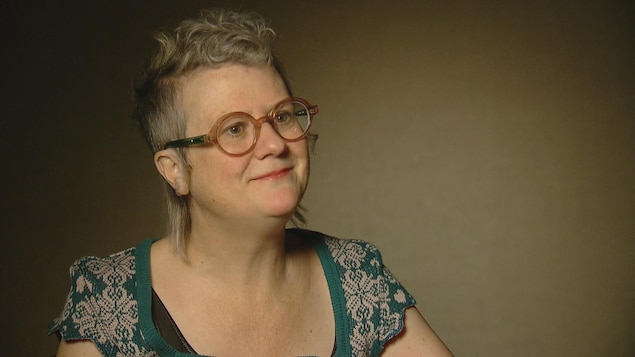 Une femme assise en entrevue à la caméra.