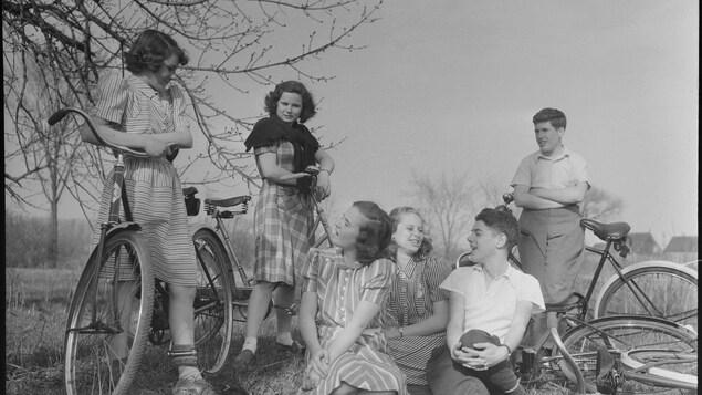 Photo en noir et blanc montrant quatre adolescentes et deux adolescents en compagnie de leur vélo.