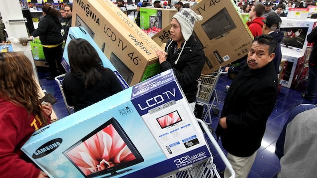 Des clients dans un magasin d'électronique attendent en file à la caisse pour payer. La plupart ont acheté une télévision.