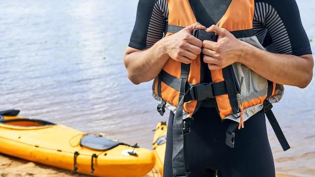 Un kayakiste est en train d'attacher sa veste de flottaison sur le bord d'un lac.