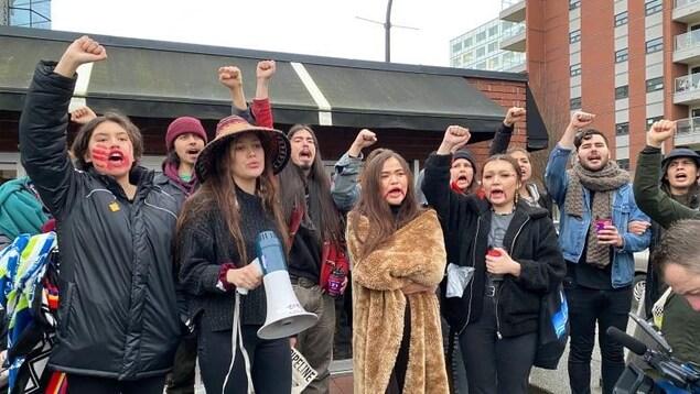 Des jeunes avec de la peinture rouge sur le visage sont en train de manifester dans la rue.