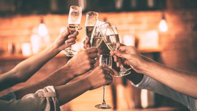 Un groupe de personnes trinque avec des flûtes de champagne.