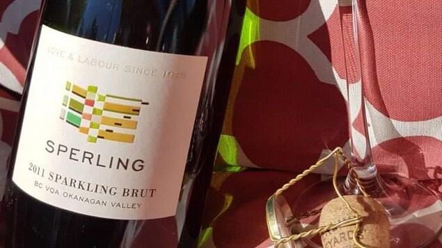 Une bouteille de vin sur une table et à côté, une coupe de champagne.