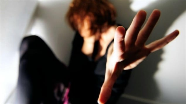 Une femme accroupie dans un coin d'une pièce, levant la main pour se protéger.