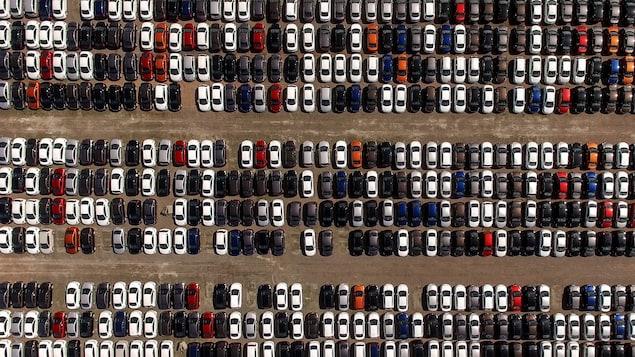Vue aérienne d'un stationnement de voitures neuves.