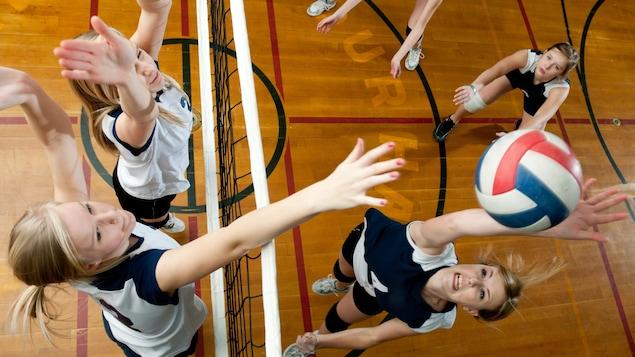 Des adolescentes en train de jouer au volleyball dans un gymnase.