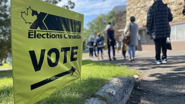 Une affiche indiquant la direction d'un bureau de vote en avant-plan et une file d'attente en arrière-plan.