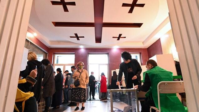 Des Géorgiens viennent déposer le bulletin de vote, dans un bureau de vote de la capitale Tbilisi, le 31 octobre.