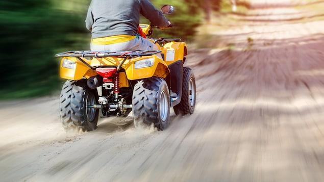 L'arrière d'un VTT roulant sur un chemin de terre.