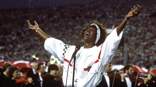 Elle a les mains levées au ciel et porte un ensemble de sport.