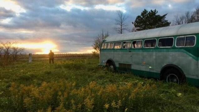 Un bus sur un terrain vert. On y voit un homme au loin.