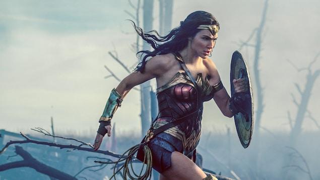 L'actrice Gal Gadot dans le costume de Wonder Woman court dans une forêt enfumée, bouclier sur le bras gauche.