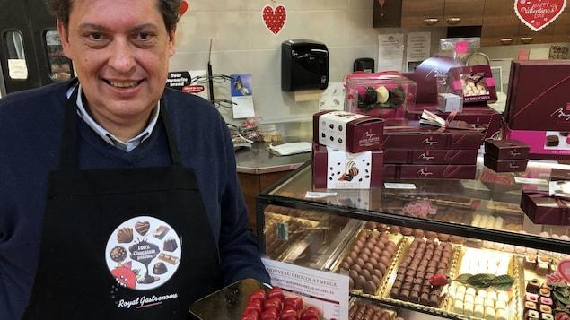 Un homme est debout devant un étalage de chocolats belges et tient un plateau de chocolats dans sa main droite.
