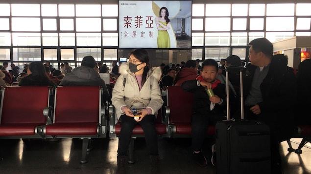 Une femme portant un masque attend de prendre le train pour Wuhan, en Chine.
