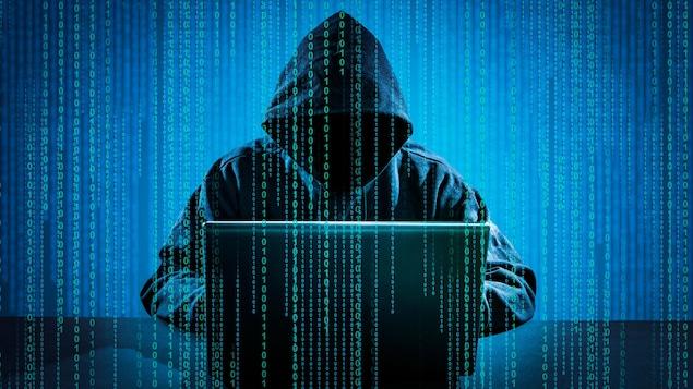 Une personne portant une capuche derrière un ordinateur.