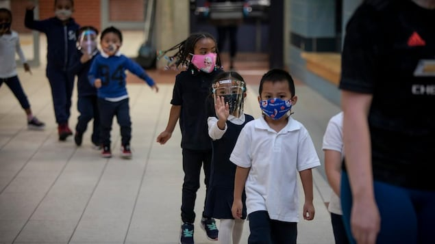 Une file de jeunes élèves qui marchent derrière un adulte dans une école.