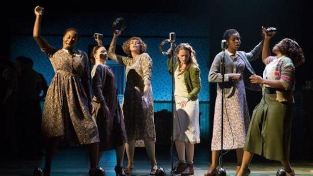 6 femmes chantent et dansent devant des microphones.