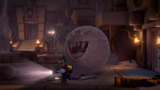 Le personnage de Luigi, muni d'une lampe de poche, se promène dans un tableau de jeu.