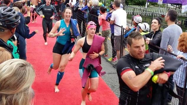 Marie-Hélène Ratel (en bleu) et d'autres participants au Ironman 70.3 de Mont-Tremblant courent sur un tapis rouge.