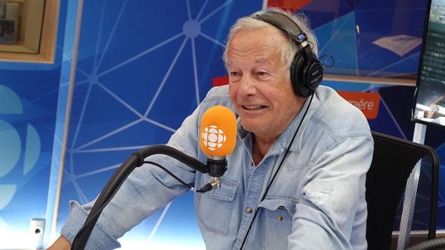 Un homme sourit en regardant vers la gauche devant un micro orange dans un studio de radio.