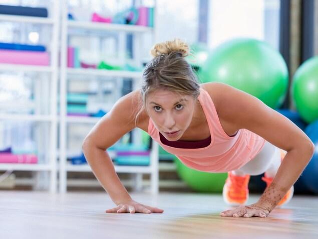 Une jeune femme fait des push-ups dans un gymnase.