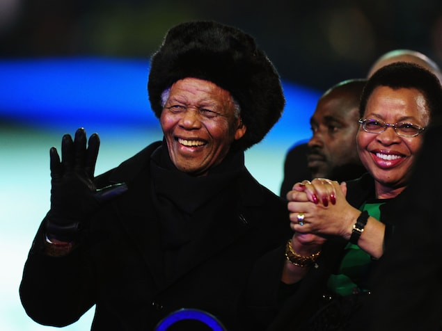 L'ancien président sud-africain Nelson Mandela salue la foule en compagnie de sa femme Graça Machel lors de la Coupe du Monde de 2010, en Afrique du Sud.