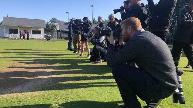 Une horde de photojournalistes alignés sur du gazon vert en train de prendre des photos.