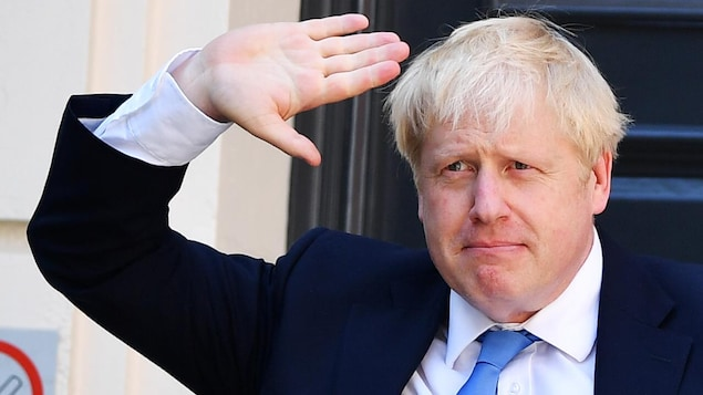 Boris Johnson lève la main en guise de salut.
