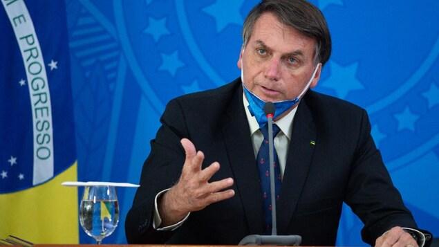 Le président du Brésil est assis. Il porte un masque, mais il l'a baissé pour mieux parler aux journalistes.