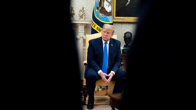 Donald Trump, assis avec les mains presques jointes. Le président semble être aperçu par le trou d'un serrure.