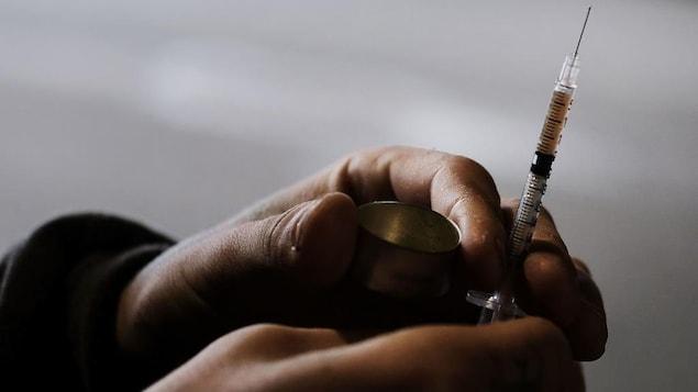 Deux mains qui tiennent une seringue.