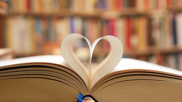 Un livre ouvert dont les pages pliées forment un coeur.