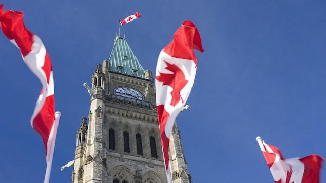 La Tour de la Paix du Parlement du Canada. Des drapeaux du Canada flottent dans le vent.