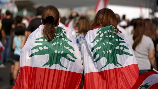 Deux femmes dans une foule sont habillées du drapeau du Liban.
