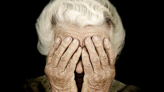 Une dame âgée se couvrant les yeux de ses mains.