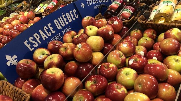 Des pommes dans un supermarché, devant une affiche « espace Québec »