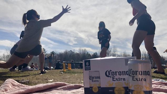 Un groupe de femmes joue au Spikeball, un jeu qui inclut une balle à faire rebondir sur un trampoline. Une caisse de bière Corona est installée en avant-plan.