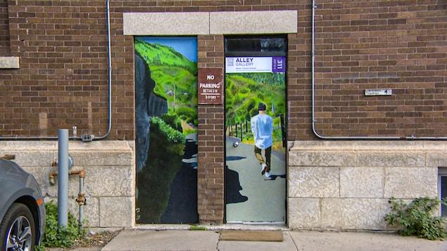Une porte derrière une édifice du centre-ville de Saskatoon est peinturée en véritable oeuvre d'art.