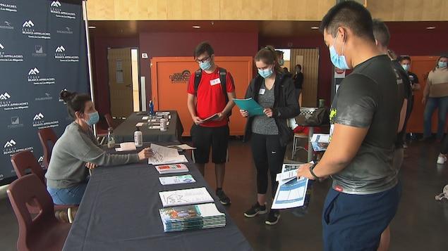 Des jeunes lisent des brochures d'informations sur le programme collégial
