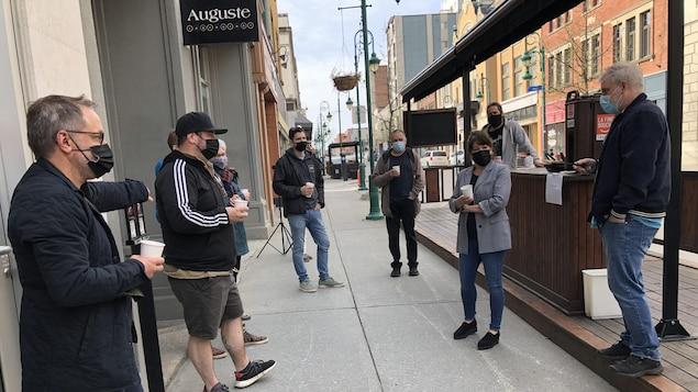Une quinzaine de restaurateurs discutent, café à la main, devant le restaurant Auguste de Sherbrooke.
