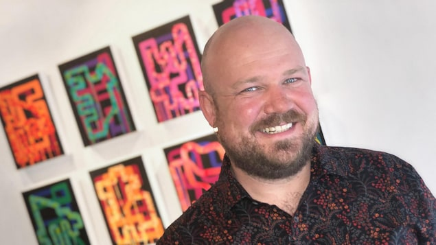 Benjamin Rodger, souriant, devant des toiles sur un mur de galerie.