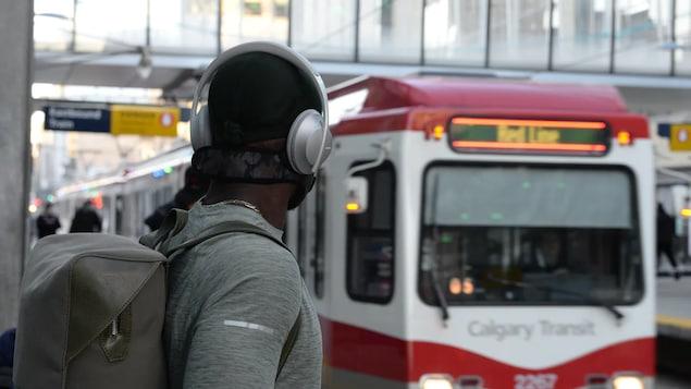 Un homme patiente à une station de Calgary Transit.
